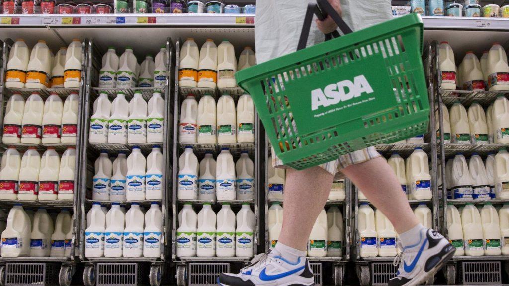 A shopper walks past milk cartons in an aisle of Asda supermarket in London, August 17, 2015.